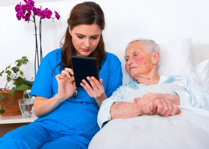 nurse-typing-notes-into-meetcaregivers-family-care-portal-on-her-tablet