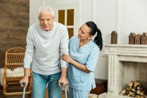 Home Care - A Nice Lady Helping A Nice Man
