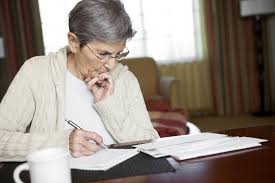 Home Care Services - A Senior Looking At Paperwork