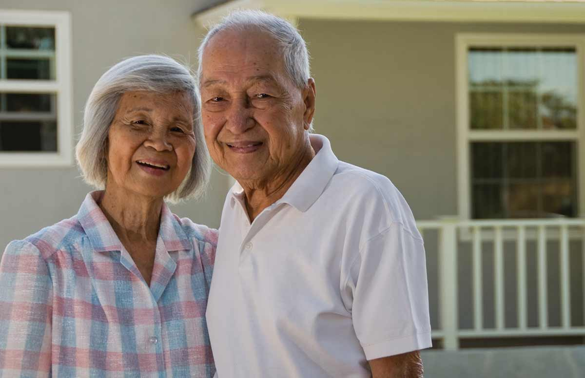 Aging In Place - An Elderly Asian Couple In Front Of Their Home