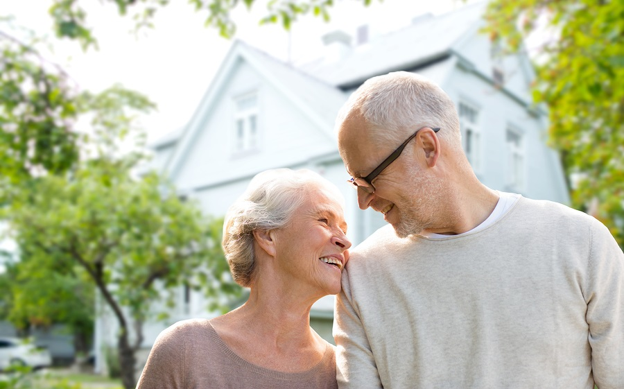 Aging In Place - A Senior Couple Standing In Front Of Their Home