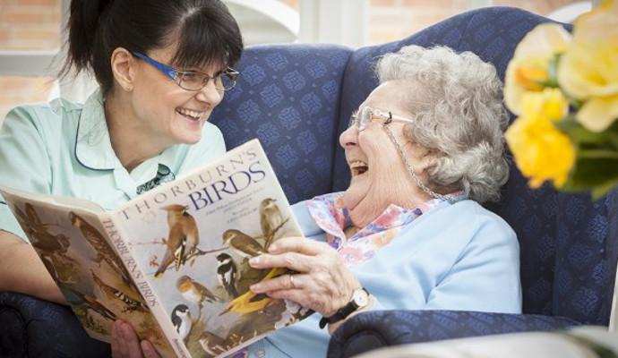 Elder Care Benefits - Caregiver Reading With Elder