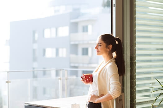 Respite Care - Woman Leaning Against Window With Mug