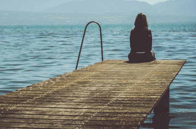 Senior Social Isolation - Woman Sitting Alone On A Dock