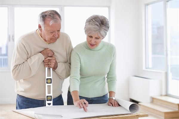 Aging In Place - Senior Couple Standing Over Blueprints