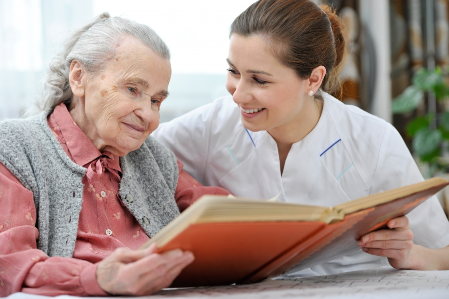Dementia Care - A Caregiver Reading To A Senior