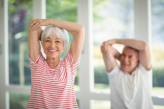 Indoor Exercises For Seniors - Elderly Couple Stretching