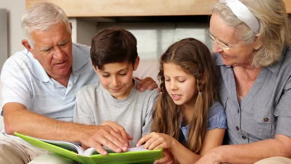 Summer Activities To Do With The Grandkids - Grandparents Looking At A Book With Grandchildren