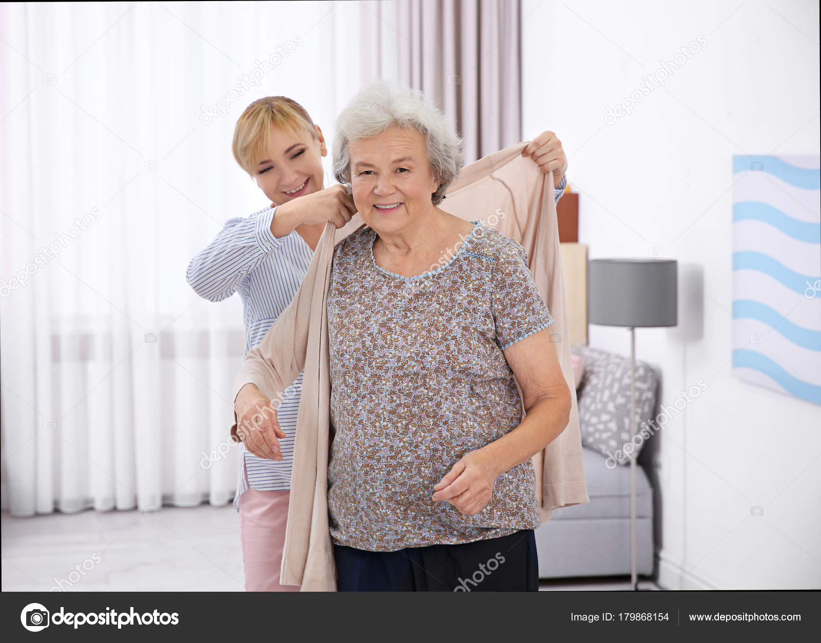 Depression In The Elderly - A Caregiver Helping An Elderly Woman Dress