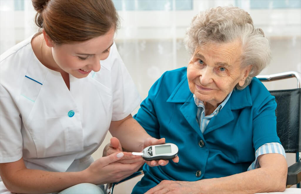 Diabetes In Seniors - A Nurse Checking An Elderly Woman's Blood Sugar