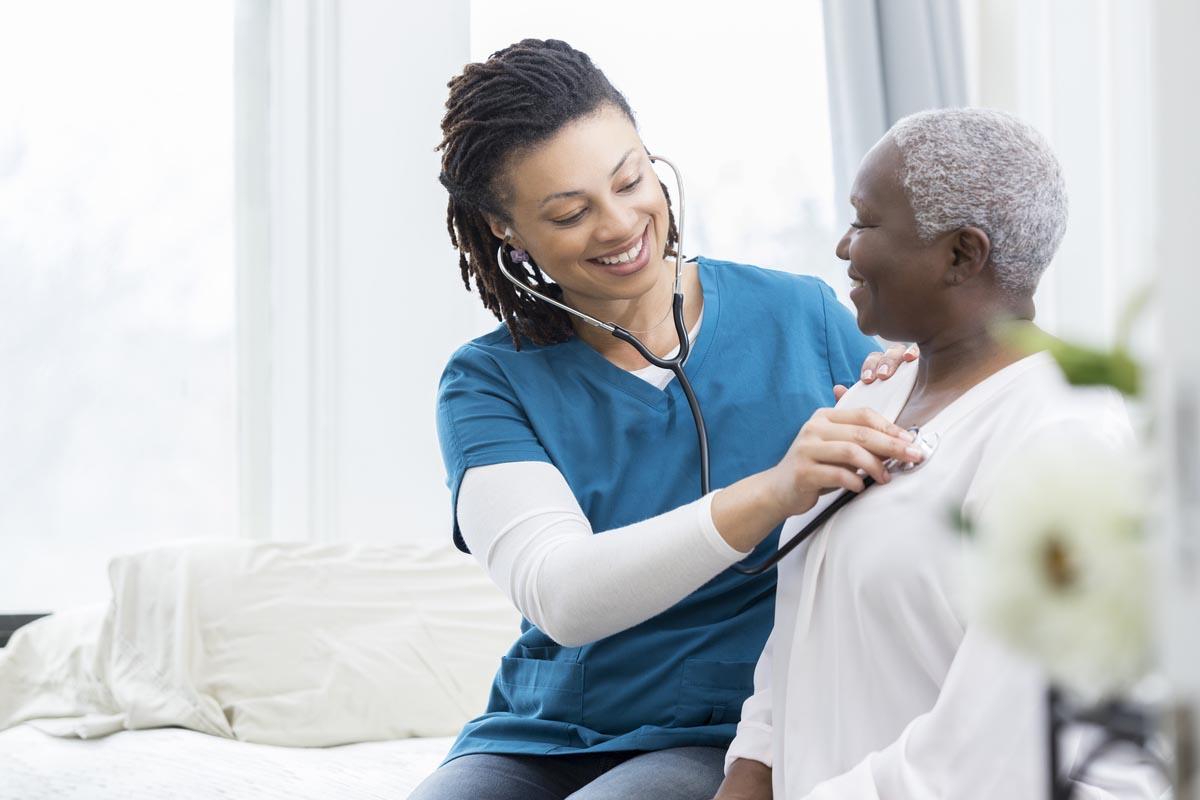 Senior Health Care - A Nurse Checking An Elderly Woman's Heart