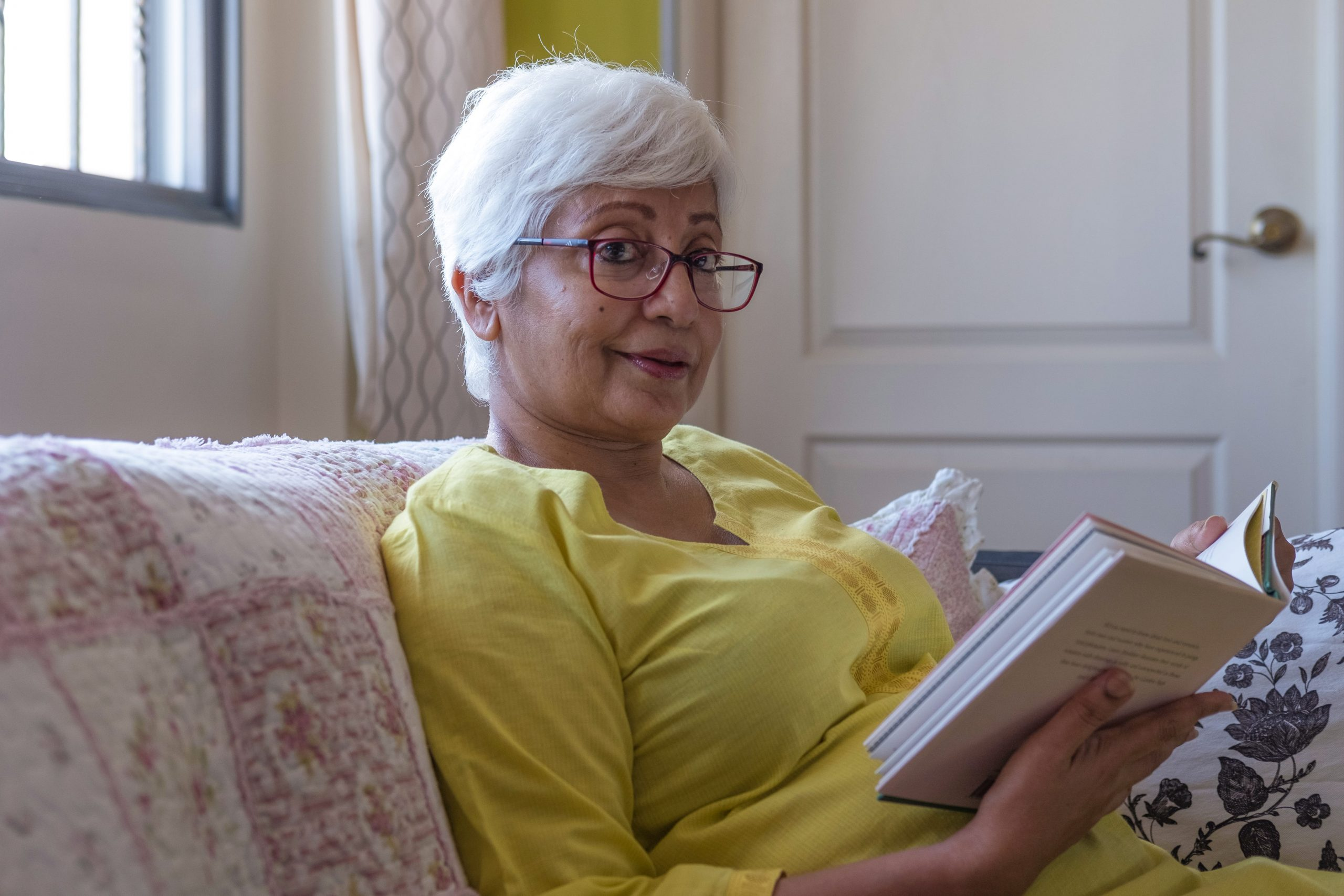 Activities For Seniors - Older Woman Reading A Book While Sitting On The Sofa