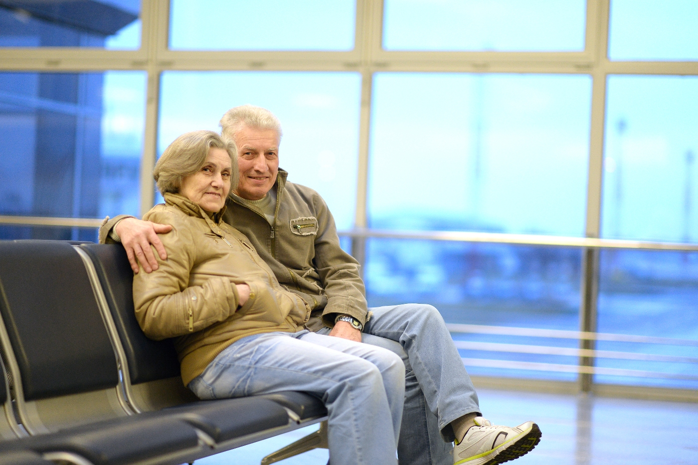Senior Travel - Senior Couple Sitting At Their Gate In The Airport