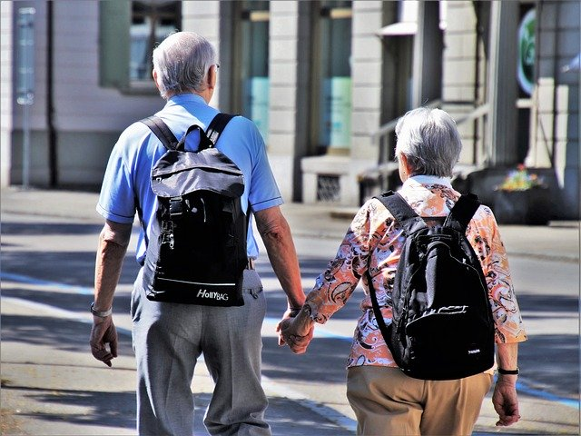 Senior Travel - An Elderly Couple Holding Hands While Touring A City