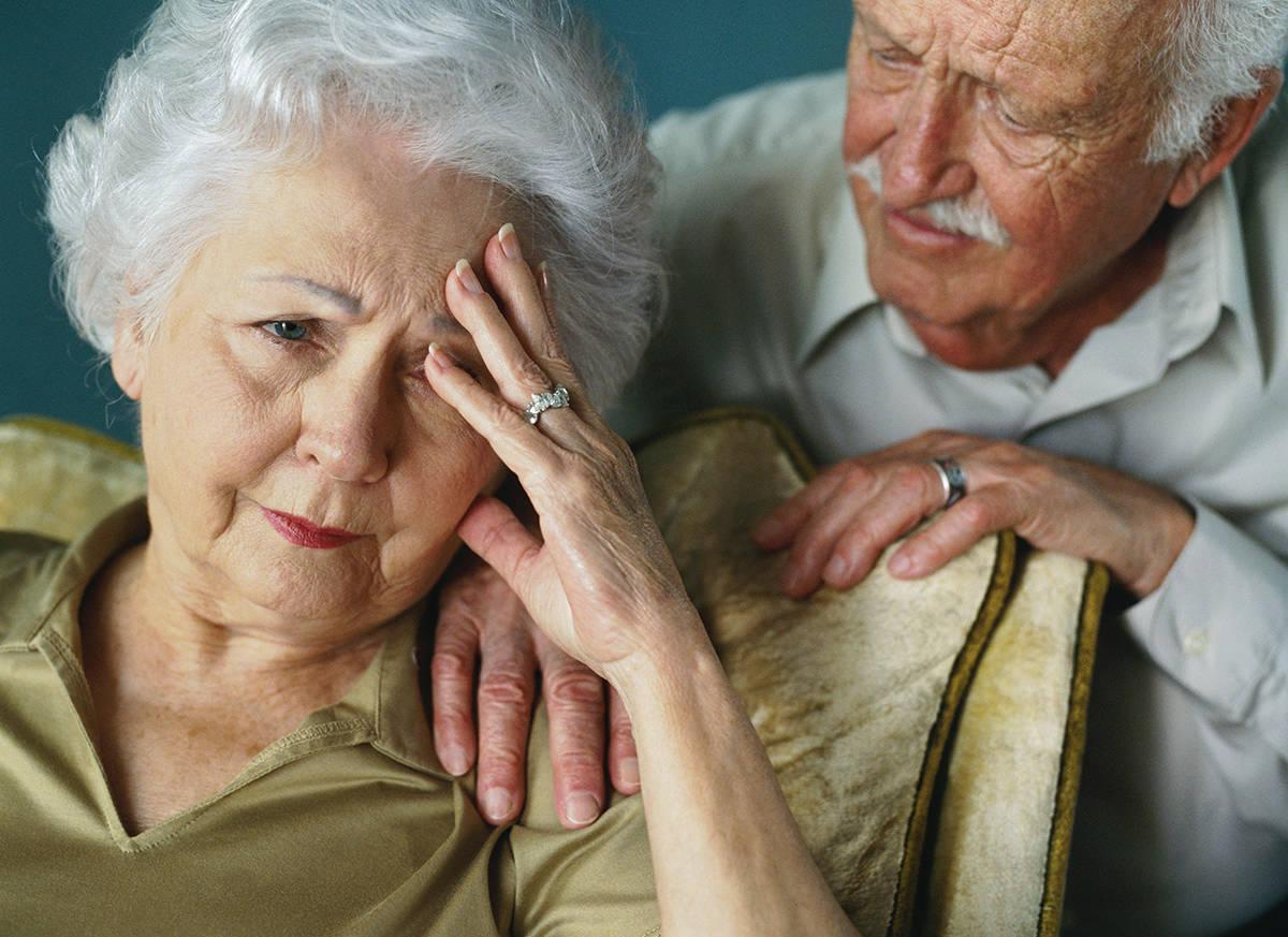 mental-health-month-an-elderly-woman-resting-her-head-in-her-hand-with-her-worried-husband-standing-behind-her