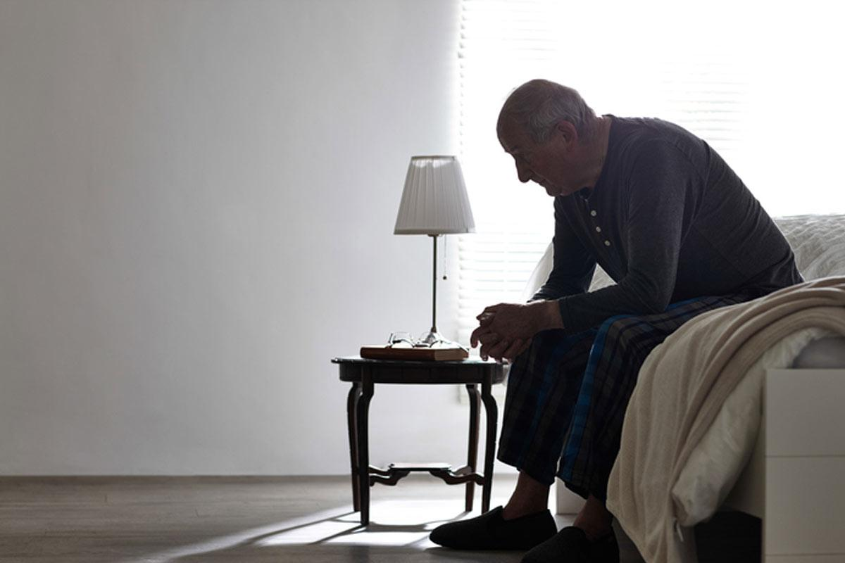 Depression In The Elderly - Elderly Man Sitting Alone On The Edge Of His Bed