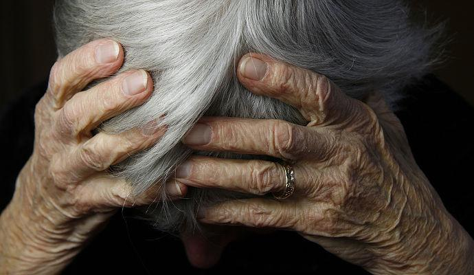Elder Abuse - An Elderly Person Holding Their Head In Their Hands