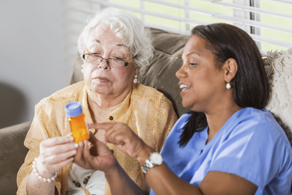 Health Literacy - Elderly Woman And Nurse Discussing Medication