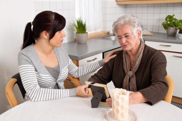 counseling-awareness-month-a-woman-talking-to-an-older-woman-looking-at-a-picture-sitting-at-a-kitchen-table