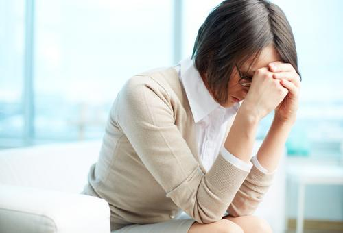 caregiver-burnout-tired-woman-holding-her-head-in-her-hands