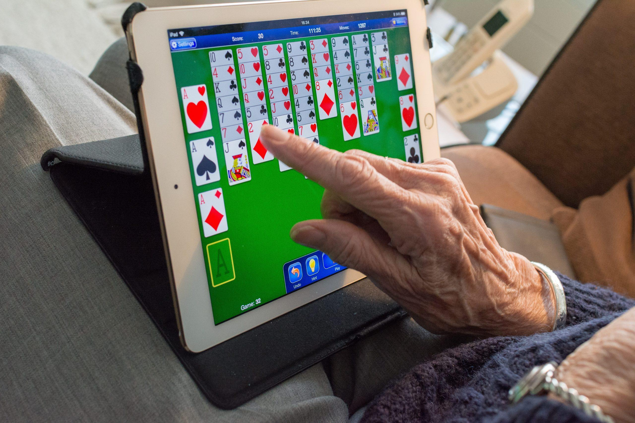 Activities for Seniors - An Older Adult Playing Cards On A Tablet