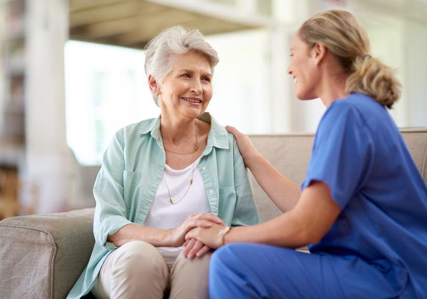 counseling-awareness-month-a-nurse-talking-to-an-older-adult-sitting-on-the-couch