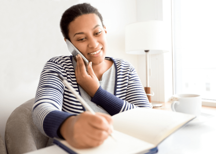 woman-talking-on-phone-about-self-directed-home-care-while-writing-notes