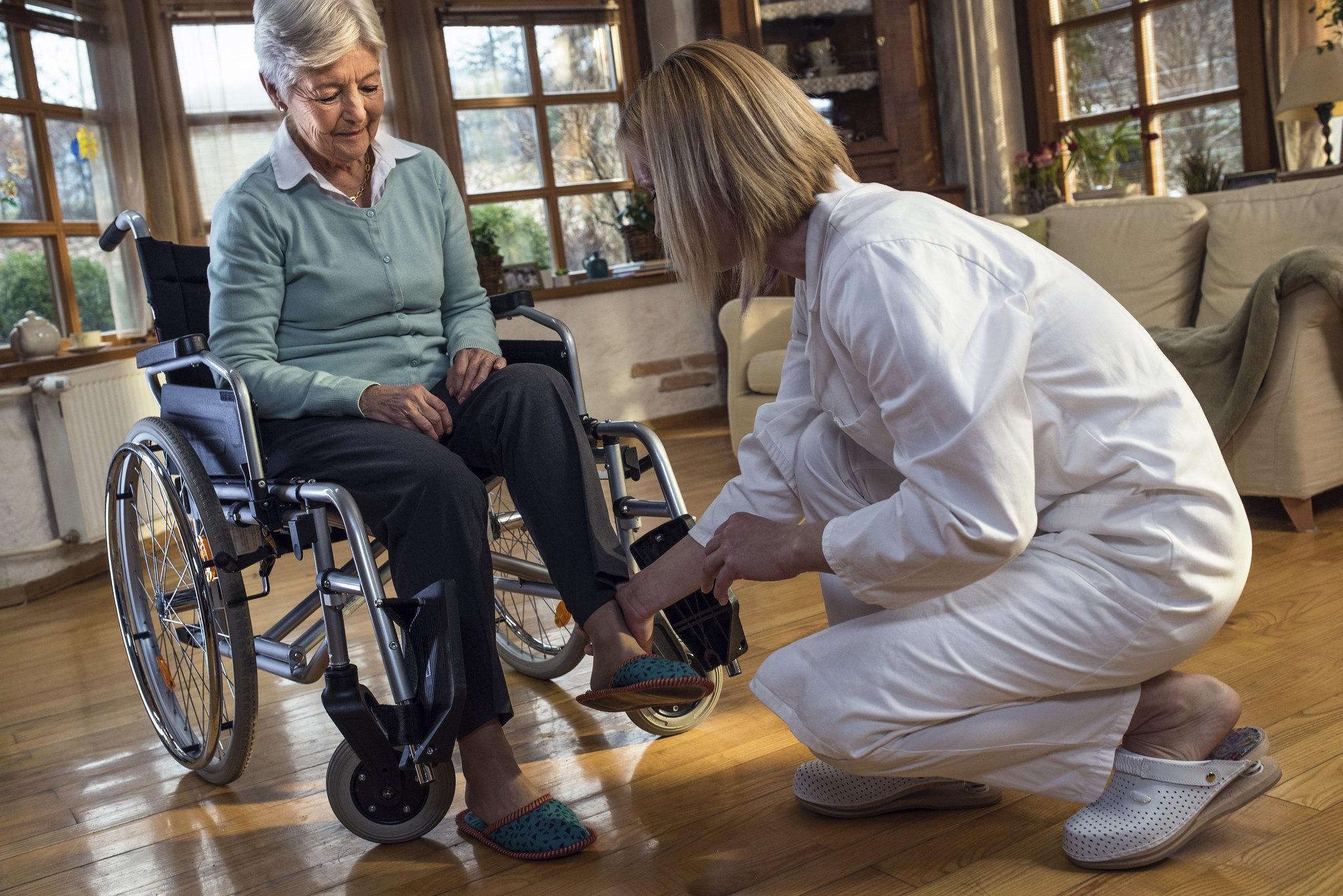 Nurse-with-senior-woman-in-wheelchair-at-home