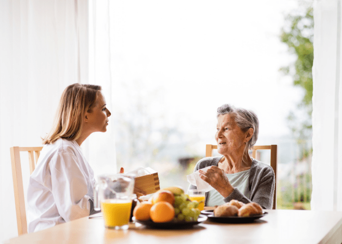 young-woman-chatting-with-elderly-woman-at-the-breakfast-table