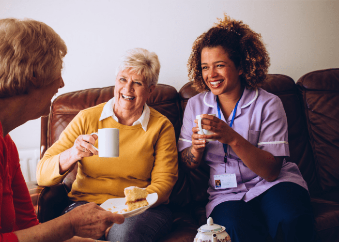 caregiver-certification-nurse-having-tea-with-two-elderly-women
