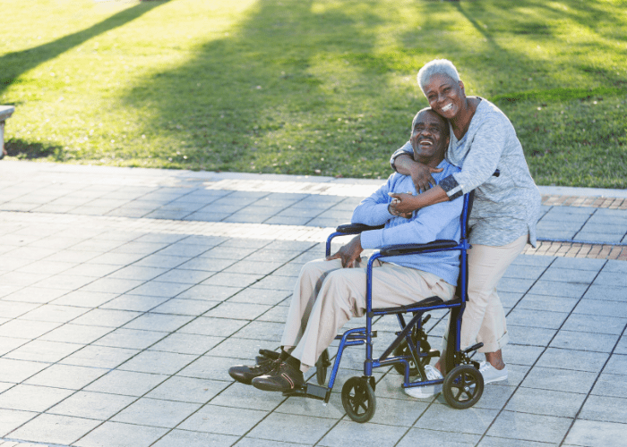senior-woman-hugging-her-elderly-husband-in-a-wheelchair-from-behind