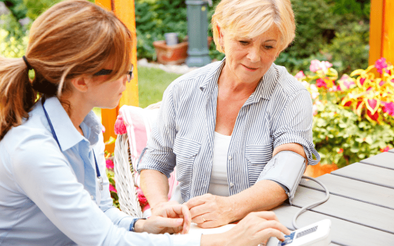 massachusetts-caregiver-taking-to-older-woman's-blood-pressure-outdoors