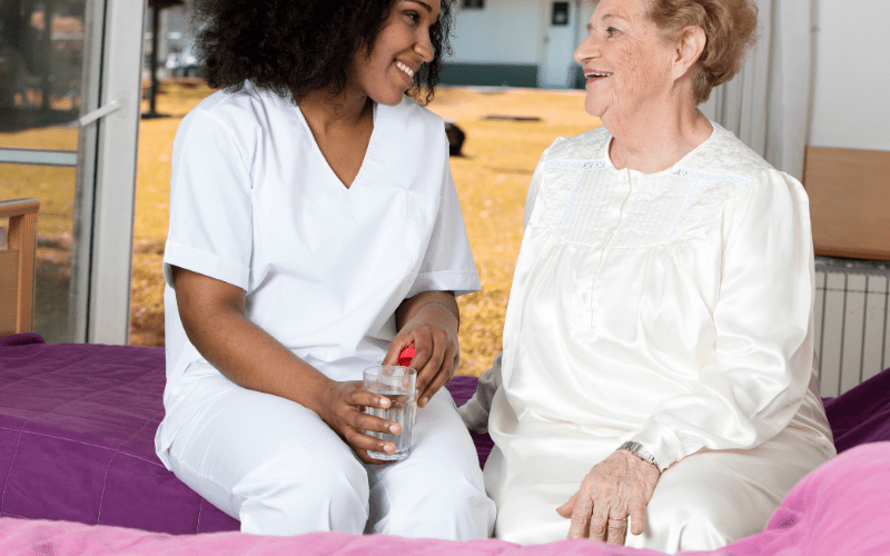 massachusetts-caregiver-talking-to-elderly-patient-in-her-room