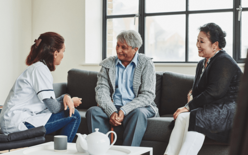 nurse-talking-to-older-couple-about-the-benefits-of-hiring-a-caregiver-for-in-home-help
