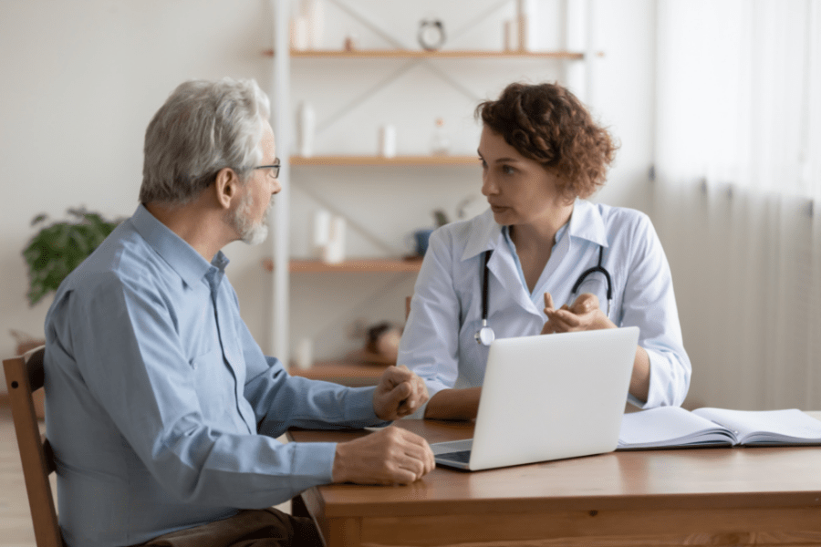 A doctor and middle aged man intensely discussing caring for elderly parents in front of a laptop and book