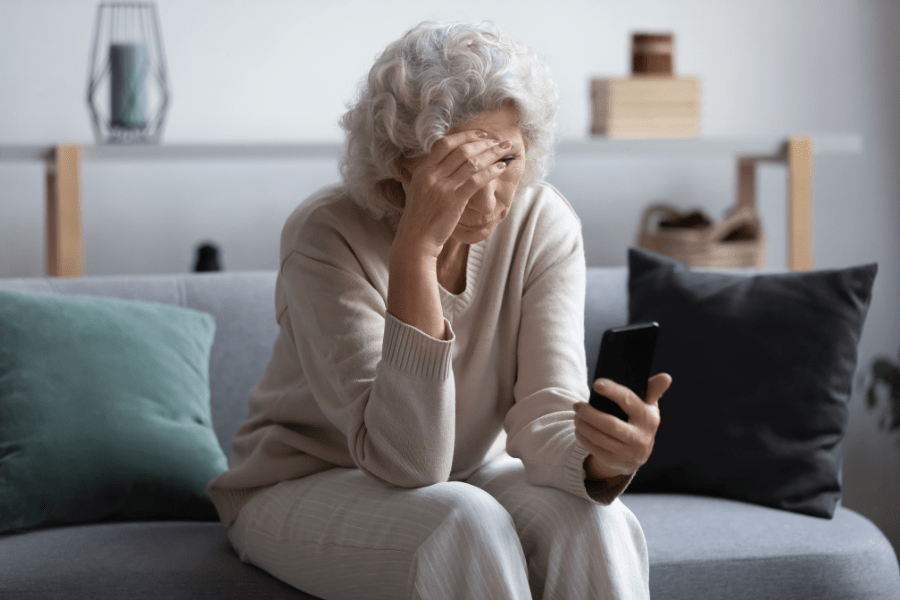 older-woman-with-compassion-fatigue-looking-at-her-phone-on-the-couch