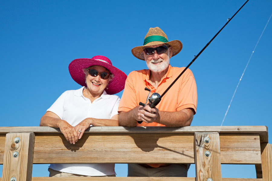 senior-couple-obversving-uv-safety-awareness-month-by-wearing-sunhats-and-sunglassess-while-fishing